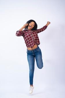 Gelukkige mooie jonge afrikaanse dames die een telefoongesprek voeren, springen van opwinding
