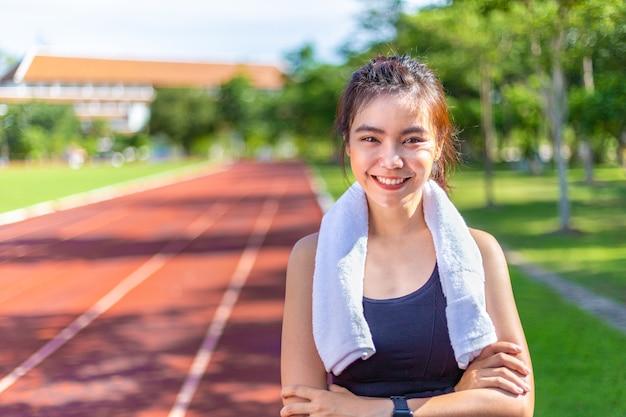 Gelukkige mooie jonge aziatische vrouw die in de ochtend uitoefent