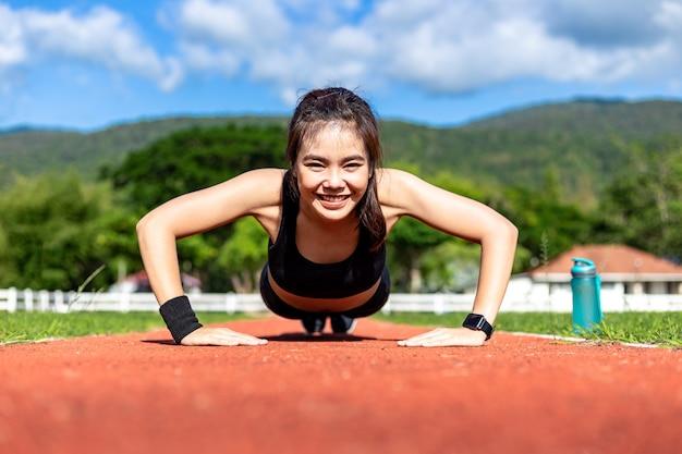 Gelukkige mooie jonge aziatische vrouw die opdrukoefeningoefening in de ochtend doen bij een renbaan op een heldere zonnige dag