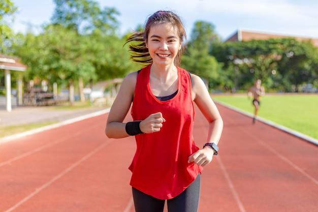 Gelukkige mooie jonge aziatische vrouw in rode oefeningsuitrusting die in de ochtend loopt