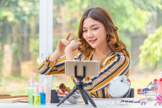 Gelukkige mooie jonge aziatische vrouw, vlogger, die schoonheidsproducten beoordeelt via haar online videoblog vanuit haar huis