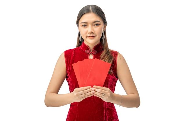 Gelukkige mooie jonge chinese vrouw die in rode chinese kleding rode geldenveloppen op wit houdt