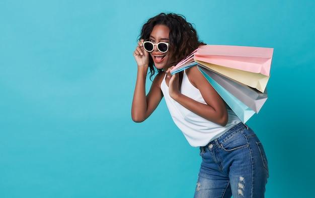 Gelukkige mooie jonge die de holding van de vrouwenhand het winkelen zak over blauwe achtergrond wordt geïsoleerd.