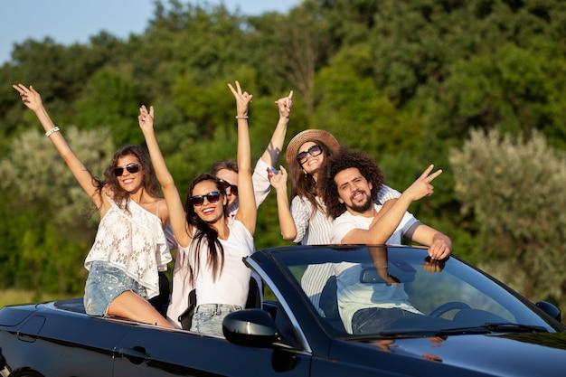 Gelukkige mooie jonge donkerharige meisjes en jongens in zonnebrillen glimlachen in een zwarte cabriolet op de weg die hun handen omhoog houden op een zonnige dag. .