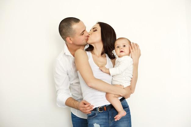 Gelukkige mooie jonge familie met het pasgeboren baby glimlachen omhelzend het kussen stellen over witte muur.