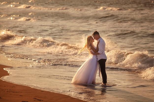Gelukkige mooie jonge paar in trouwjurk en pak aan zee bij zonsondergang, golven