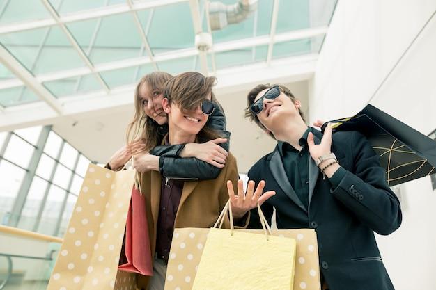 Gelukkige mooie jonge paarholding het winkelen zakken terwijl status in wandelgalerij. vrouw pickaback