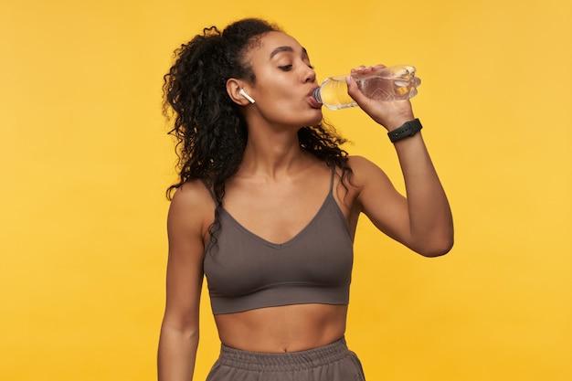 Gelukkige mooie jonge sportvrouw die naar muziek luistert met behulp van draadloze oortelefoons en drinkwater uit een fles geïsoleerd over gele muur yellow