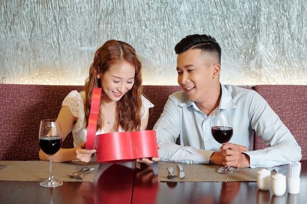 Gelukkige mooie jonge vrouw die een geschenkdoos in de vorm van een hart opent van haar vriend wanneer ze een date hebben in een restaurant Premium Foto