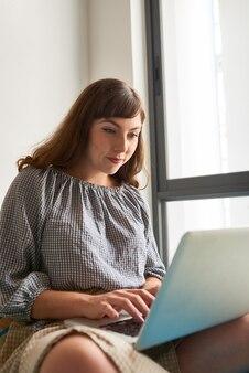 Gelukkige mooie jonge vrouw die op laptop werkt of e-mails beantwoordt terwijl ze op de vensterbank zit