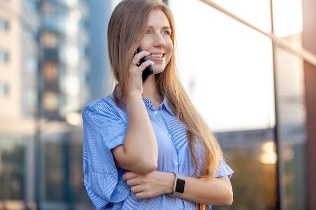 Gelukkige mooie jonge vrouw die op mobiele telefoon dichtbij de bureauvensters spreekt