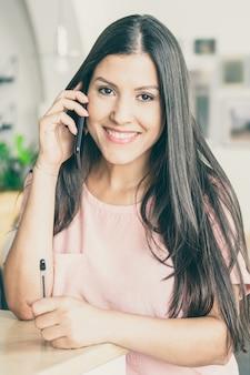 Gelukkige mooie jonge vrouw die op mobiele telefoon spreekt, die zich bij co-working bevindt, leunend op bureau