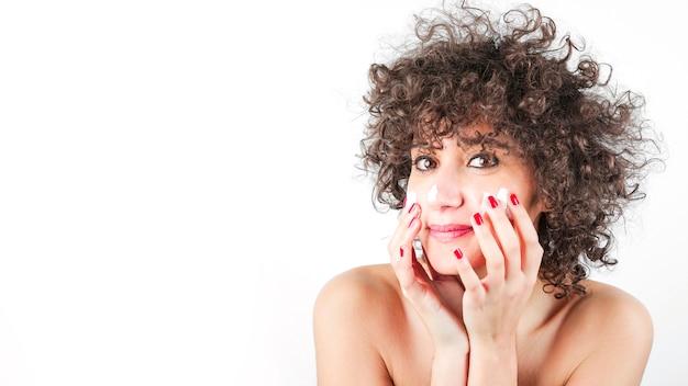 Gelukkige mooie jonge vrouw die vochtinbrengende crème op haar gezicht toepast tegen witte achtergrond
