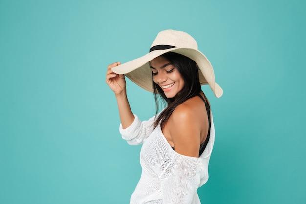 Gelukkige mooie jonge vrouw in en hoed die bevindt zich glimlacht