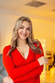 Gelukkige mooie jonge vrouw met glimlach in elegante rode jurk met halslijn binnenshuis, weekendfeest