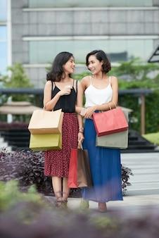 Gelukkige mooie jonge vrouwen die buiten lopen na het kopen van veel schoenen, kleding en cosmetica in de uitverkoop ...
