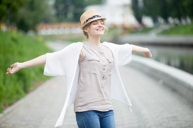 Gelukkige mooie kaukasische vrouw in de zomer voelen vreugdevolle buitenshuis