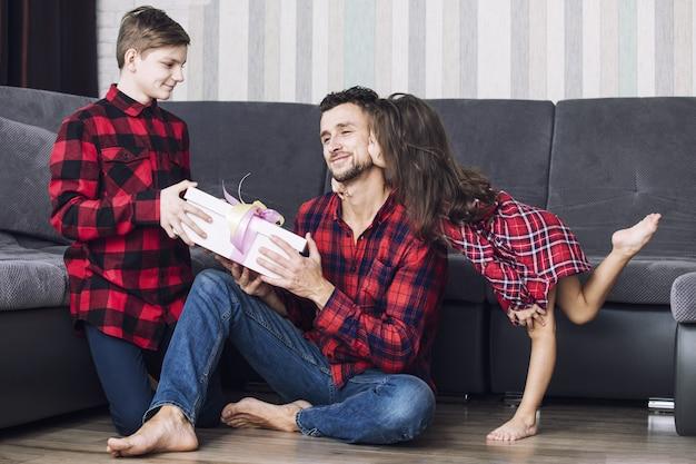 Gelukkige mooie kinderen, een jongen en een meisje, geven bij de gelegenheid samen thuis in de woonkamer een cadeau aan de vader
