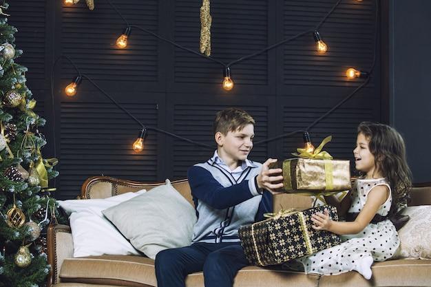 Gelukkige mooie kinderen jongen en meisje met geschenken om thuis samen kerstmis te vieren