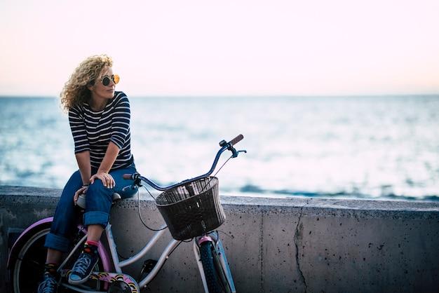 Gelukkige mooie krullende gezonde blanke volwassen vrouw van middelbare leeftijd gaat zitten op een vintage gekleurde fiets en geniet van de oceaan in vrijetijdsbesteding in de buitenlucht