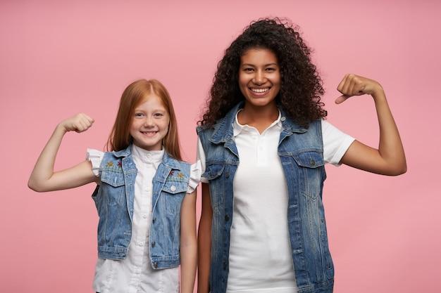 Gelukkige mooie langharige jonge meisjes in casual look die hun handen opsteken en hun kracht tonen, vrolijk kijkend met een charmante glimlach, staand tegen roze