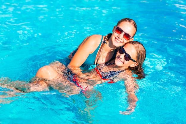 Gelukkige mooie meisjes die plezier hebben bij het zwembad van het resort