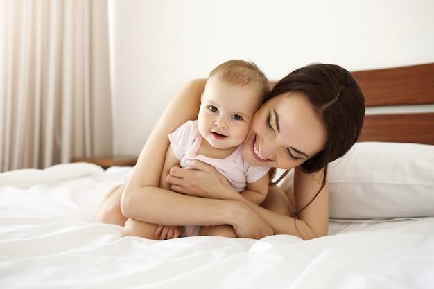 Gelukkige mooie moeder in nachtkleding die op bed met haar babydochter ligt die het glimlachen omhelst.