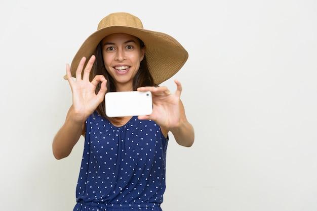 Gelukkige mooie multi-etnische toeristenvrouw die foto met telefoon neemt en ok teken geeft