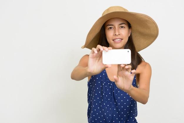 Gelukkige mooie multi-etnische toeristenvrouw die foto met telefoon neemt