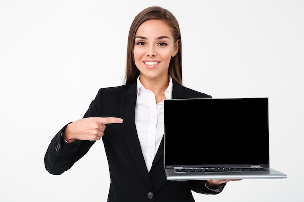 Gelukkige mooie onderneemster die vertoning van laptop toont