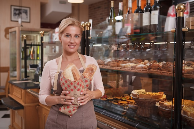 Gelukkige mooie rijpe vrouw die heerlijk brood verkoopt bij haar bakkerijwinkel, exemplaarruimte
