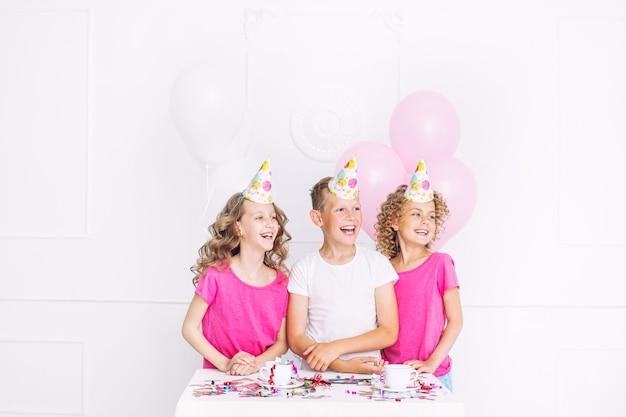 Gelukkige mooie schattige kinderen glimlachen op het vakantiefeest met ballonnen en confetti samen