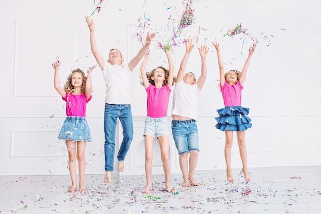 Gelukkige mooie schattige kinderen glimlachen op het vakantiefeest met confetti samen in de witte kamer