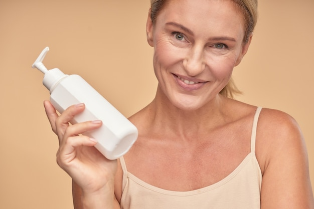 Gelukkige mooie volwassen dame die vochtinbrengende lotion toont
