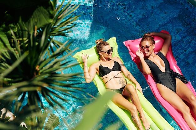 Gelukkige mooie vriendinnen in zwemkleding en zonnebrillen zonnebaden op drijvende matrassen en praten