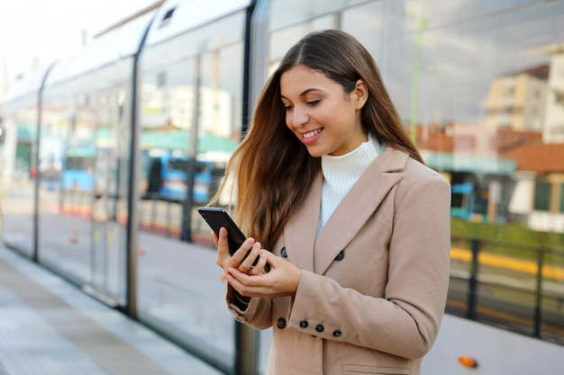 Gelukkige mooie vrouw die cellulaire het bijwerken van informatie over stadsvervoer op webpagina houdt. glimlachende zakenvrouw tevreden met online ticketservice betalen voor elektrisch vervoer via smartphone.