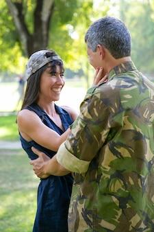 Gelukkige mooie vrouw die echtgenoot bekijkt die van leger terugkeert. vrolijke dame soldaat cup dragen, buitenshuis staan, glimlachen en omhelzen met vriendje in uniform. militair en liefdeconcept