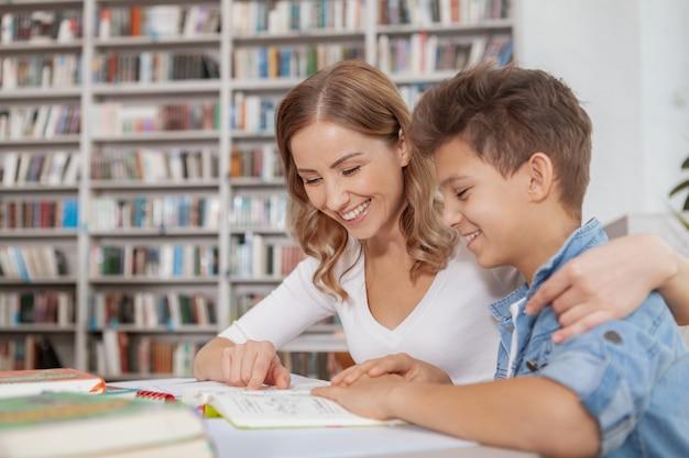 Gelukkige mooie vrouw die haar jonge zoon omhelst, die hem helpt met schoolproject bij de bibliotheek