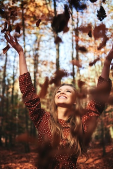 Gelukkige mooie vrouw die herfstbladeren in het bos gooit