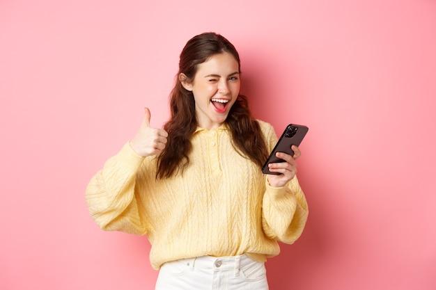 Gelukkige mooie vrouw die ja zegt, mobiele telefoon vasthoudt en duim omhoog gebaar maakt, goede zaak goedkeurt, staande tegen roze muur.