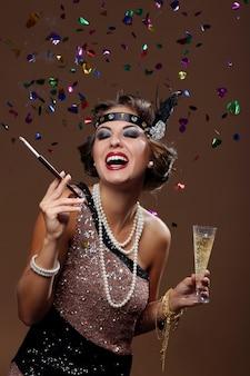 Gelukkige mooie vrouw die lacht met confettachtergrond