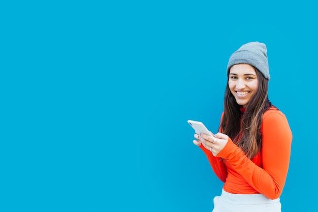 Gelukkige mooie vrouw die mobiele telefoon houdt tegen blauwe achtergrond