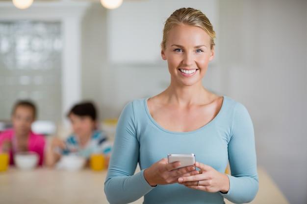 Gelukkige mooie vrouw die mobiele telefoon in keuken met behulp van
