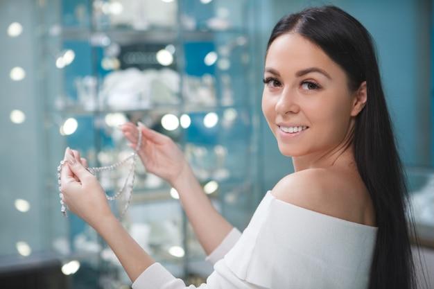 Gelukkige mooie vrouw die naar voren glimlacht, diamanten halsketting vasthoudt