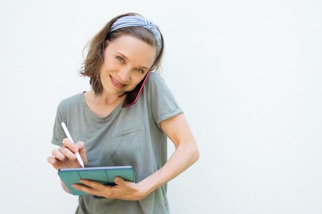 Gelukkige mooie vrouw die op het tabletscherm schrijven