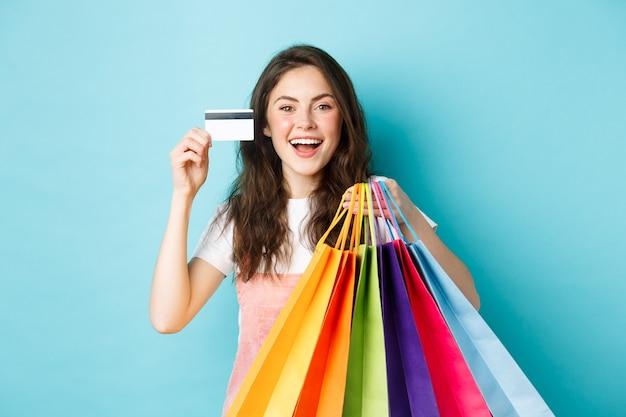 Gelukkige mooie vrouw die plastic creditcard en boodschappentassen met goederen toont, koopt met kortingen, staande over blauwe achtergrond.