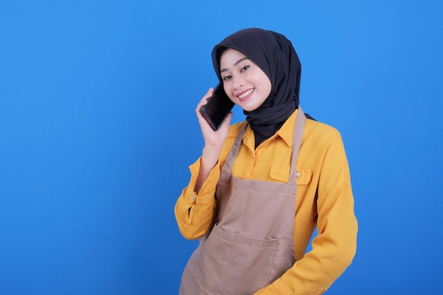 Gelukkige mooie vrouw die schort draagt die aan de telefoon spreekt