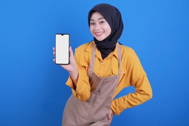 Gelukkige mooie vrouw die schort draagt die mobiele telefoon toont