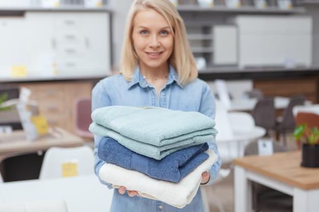 Gelukkige mooie vrouw die stapel nieuwe handdoeken standhoudt