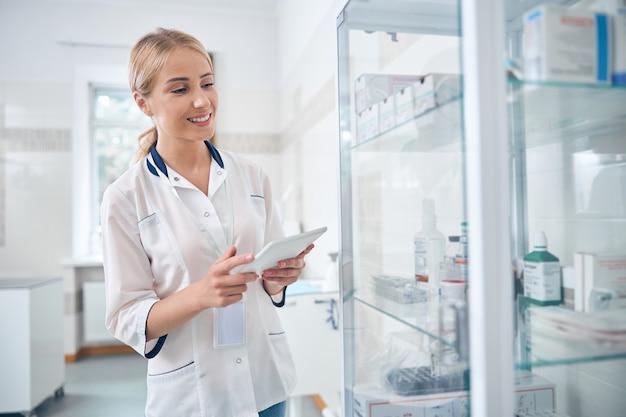 Gelukkige mooie vrouw gebruikt tablet en internet terwijl ze in de buurt van planken staat met medicijnen in de kliniek